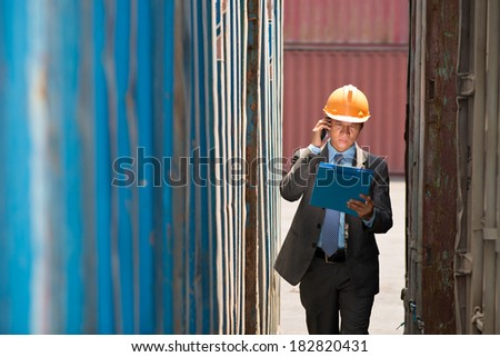 Copy-spaced image of a professional manager inspecting seaport according to the plan on the foreground  - stock photo