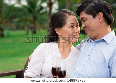 Copy-spaced image of a romantic senior couple with glasses of wine  - stock photo