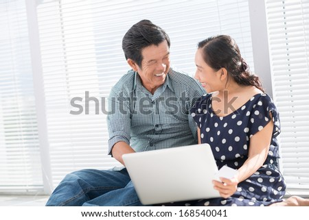 Copy-spaced image of a senior couple using laptop at home  - stock photo