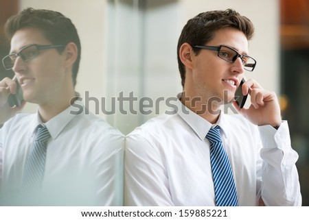 Copy-spaced image of a young businessman having business conversation by the phone inside - stock photo