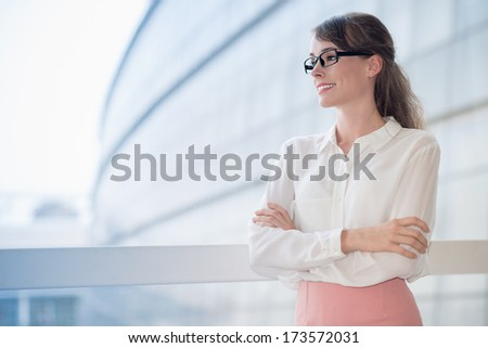Copy-spaced image of a young cheerful business lady posing at camera  - stock photo