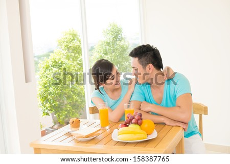 Copy-spaced image of a young couple having romantic breakfast of their weekend in the apartment - stock photo