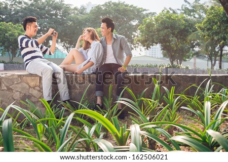 Copy-spaced image of a young couple posing at camera while their friend making a photo of them in the park - stock photo