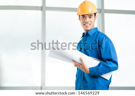 Copy-spaced image of a young foreman with blueprints  - stock photo