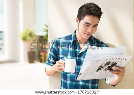Copy-spaced image of a young man reading the local news with a cup of tea on the foreground  - stock photo