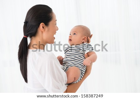 Copy-spaced image of an excited mother holding her son on hands over white - stock photo