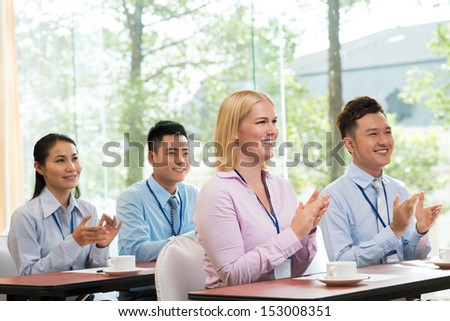 Copy-spaced image of businesspeople sitting at a table and applauding - stock photo