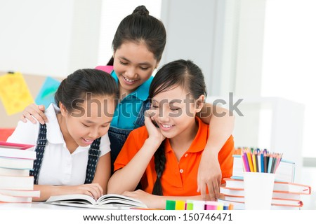 Copy-spaced image of classmates reading a book together