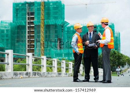 Copy-spaced image of modern engineers discussing something outside - stock photo