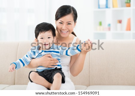 Copy-spaced portrait of a cheerful mum with her little son at home - stock photo