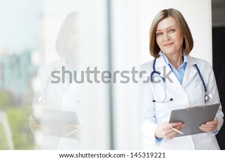 Copy-spaced portrait of a friendly general practitioner holding a medical record - stock photo