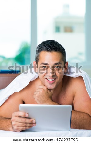 Copy-spaced portrait of a man in the bed with a touchpad  - stock photo