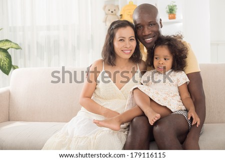 Copy-spaced portrait of a mixed family smiling and looking at camera  - stock photo