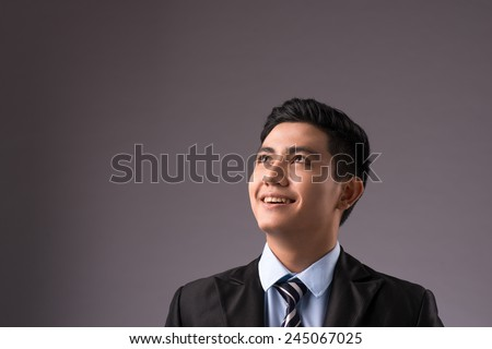 Copy-spaced portrait of a young successful businessman thinking over the business strategy over a gray background. Confident handsome asian man in suit with tie looking up.  - stock photo