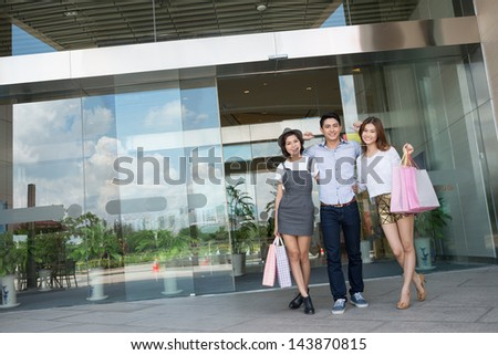 Copy-spaced portrait of joyful friends standing with shopping-bags in front of the shopping mall - stock photo