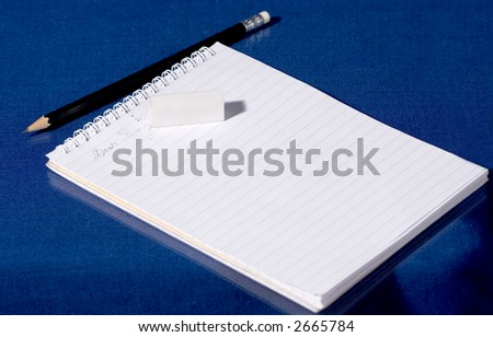 Copybook, pencil and rubber on a blue background - stock photo