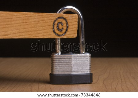 Copyright symbol on a piece of wood that is attached to a lock. - stock photo