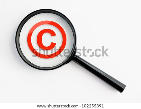 copyright symbol under a magnifying glass, with isolated background - stock photo