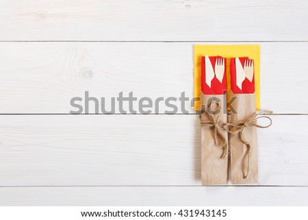 Copyspace at white wooden background for menu, plate or recipe. Food background. Fork and knife wrapped in brown paper, cutlery at wood top view with copy space. View from above - stock photo