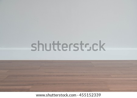 Copyspace background with an empty wall with a wooden floor below - stock photo