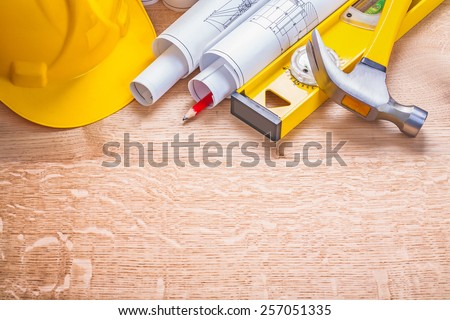 copyspace concstruction concept image helmet rolled blueprints level claw hammer on wooden boards - stock photo