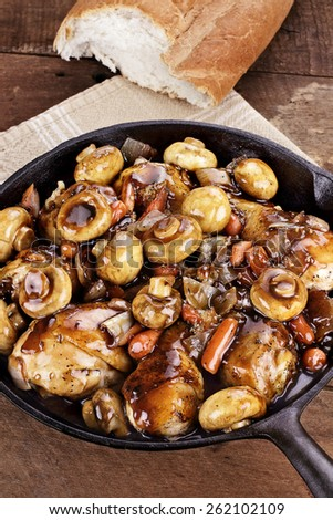 Coq Au Vin in rustic cast iron pan with shallow depth of field. - stock photo