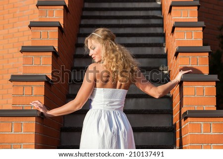 Coquettish young beautiful woman posing near the stairs at sunset.  Evening light with deep shadows and color shift - stock photo
