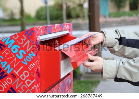 Coquitlam, BC Canada - April 24, 2014 : Hand sending a tax report letter in a red mail box  - stock photo