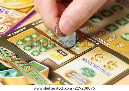 Coquitlam BC Canada - June 15, 2014 : Woman scratching lottery ticket called Monopoly. It's published by BC Lottery Corporation has provided government sanctioned lottery games.  - stock photo