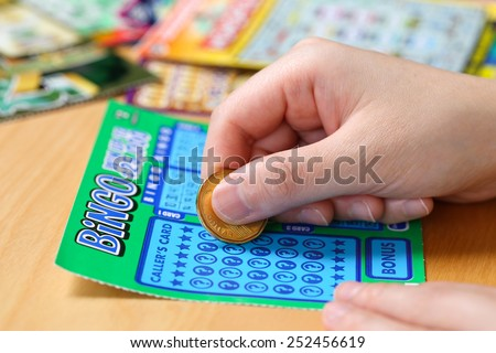 Coquitlam BC Canada - June 15, 2014 : Woman scratching lottery tickets. The British Columbia Lottery Corporation has provided government sanctioned lottery games in British Columbia since 1985.