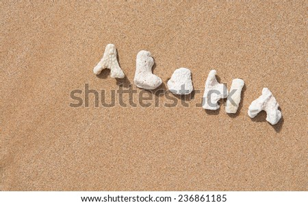 coral letters spelling out the word aloha on a beach   - stock photo
