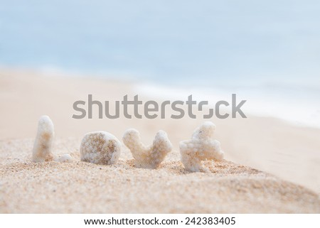 coral letters spelling the word love in the sand with blue ocean behind - stock photo