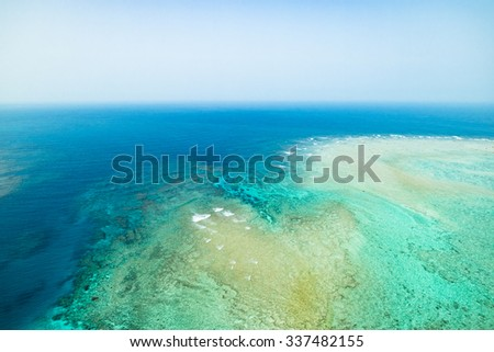 Coral reef and clear blue tropical water from above by paragliding flight, Amami Oshima Island, Kagoshima, Japan - stock photo