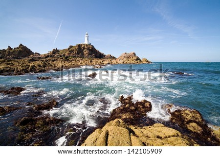 Corbiere Lighthouse and the rocky coast in Jersey, The Channel Islands - stock photo
