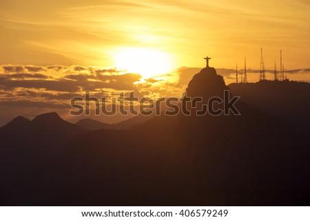 Corcovado mountain Christ the Redeemer standing in golden sunset clouds Rio de Janeiro Brazil - stock photo