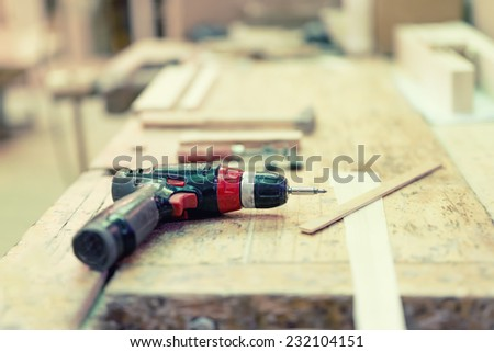 Cordless drilling screwdriver machine at industrial wood and steel factory on wooden board - stock photo