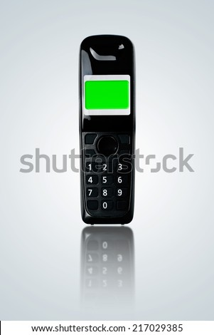 Cordless landline phone with green screen display on gray gradient background. - stock photo