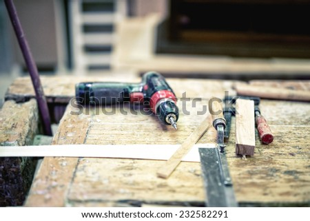 Cordless screwdriver and carpenter tools in wood industrial factory - stock photo