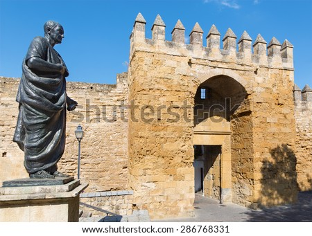 CORDOBA, SPAIN - MAY 25, 2015: The statue of philosopher Lucius Annaeus Seneca the Younger by Amadeo Ruiz Olmos (1913 - 1993) and medieval gate Puerta del Almodovar. - stock photo