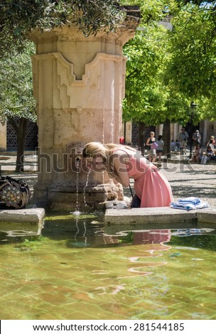 CORDOBA - SPAIN - MAY 09, 2015 - Woman drinking water and cooling from a source a hot day in Cordoba, Spain. The city of Cordoba it is located in the autonomous region of Andalucia in southern Spain - stock photo