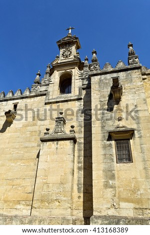CORDOBA, SPAIN - September 10, 2015: Detail of a small tower with window, coat of arms and cross on the west facade of the Mosque-Cathedral of Cordoba, on September 10, 2015 in Cordoba, Spain - stock photo