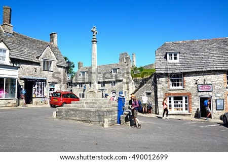 CORFE, UNITED KINGDOM - JULY 19, 2016 - Stone cross in the village centre with the castle to the rear, Corfe, Dorset, England, UK, Western Europe, July 19, 2016.
