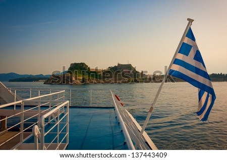 Corfu castle and Greek flag pictured in sunset from boat - stock photo