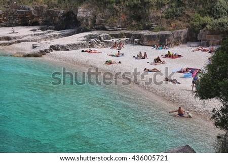 CORFU, GREECE - MAY 31, 2016: People enjoy the beach in Kassiopi, Corfu Island, Greece. 558,000 tourists visited Corfu in 2012. - stock photo