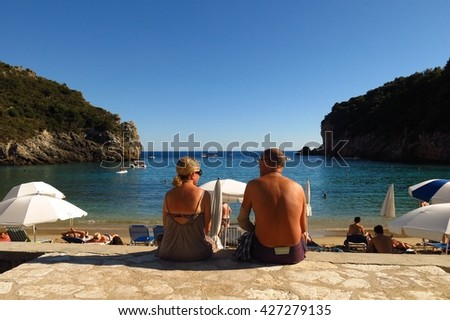 Corfu, Greece - September 3, 2014: A man and woman sit beside the beach at Paleokastritsa on Corfu, Greece. Paleokastritsa is known for its scenic coves and caves.