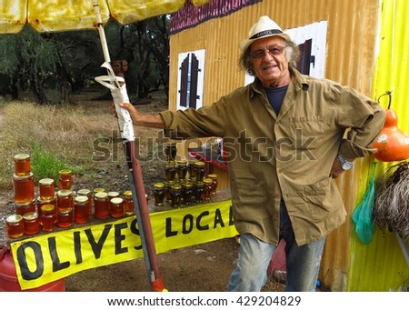 Corfu, Greece - September, 3 2014: A man sells olives and honey at a roadside stand in Corfu, Greece.