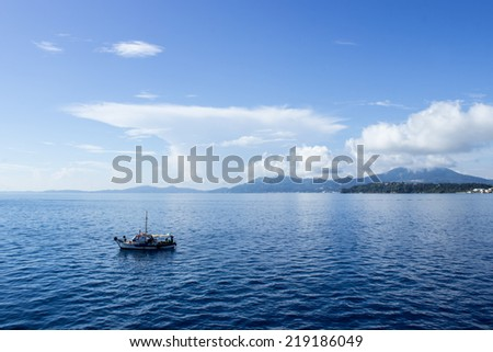 Corfu island with a small boat in front of it - stock photo