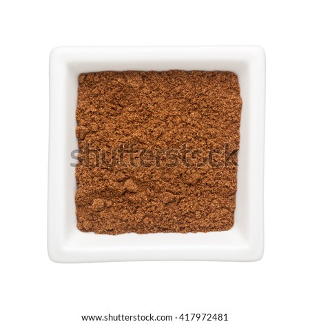 Coriander powder in a square bowl isolated on white background - stock photo