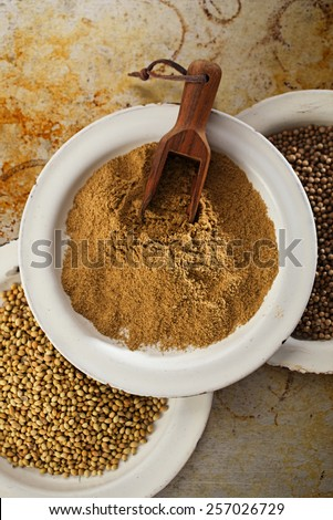 coriander powder with seeds black and white in vintage enamelled plates ... - stock photo