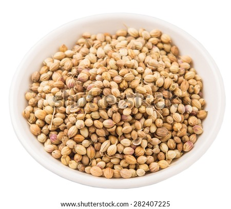 Coriander seeds in white bowl over white background - stock photo